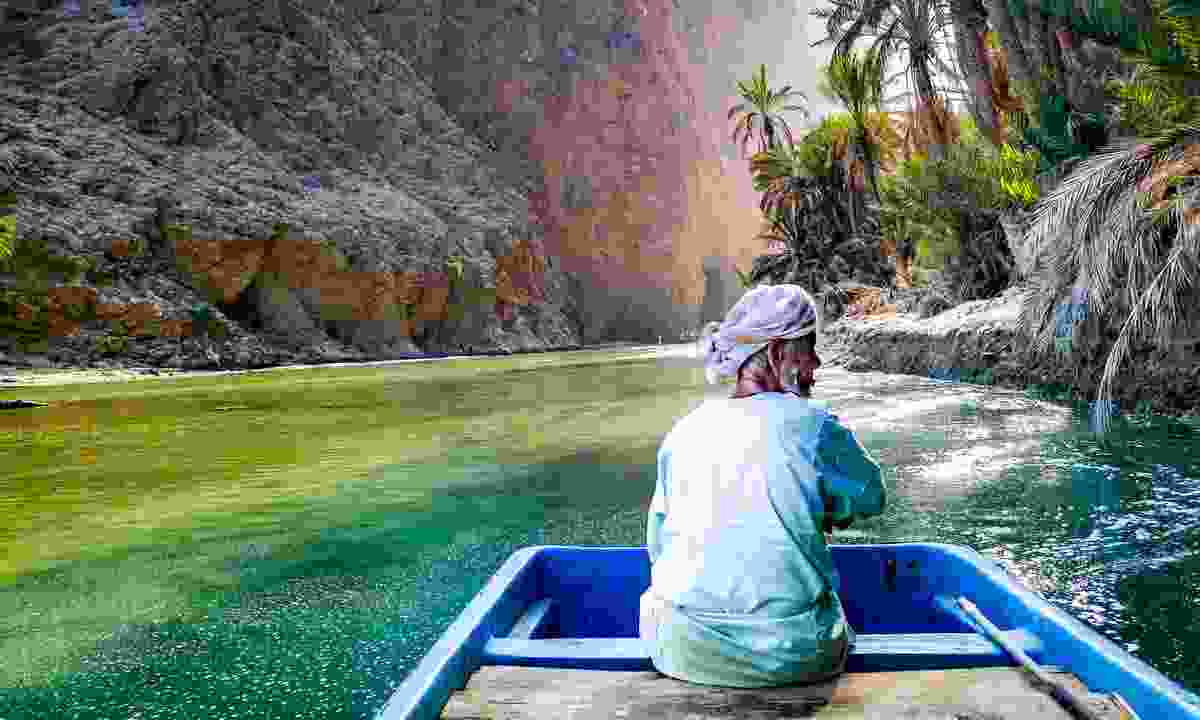 An old Omani man steering a boat in Wadi Shab (Shutterstock)