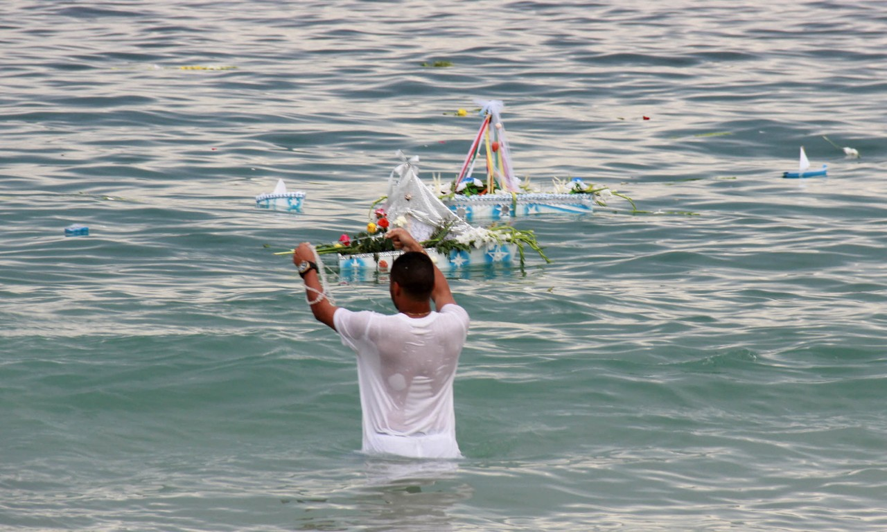 Guy setting boat in water to honour Yemanja (Dreamstime)