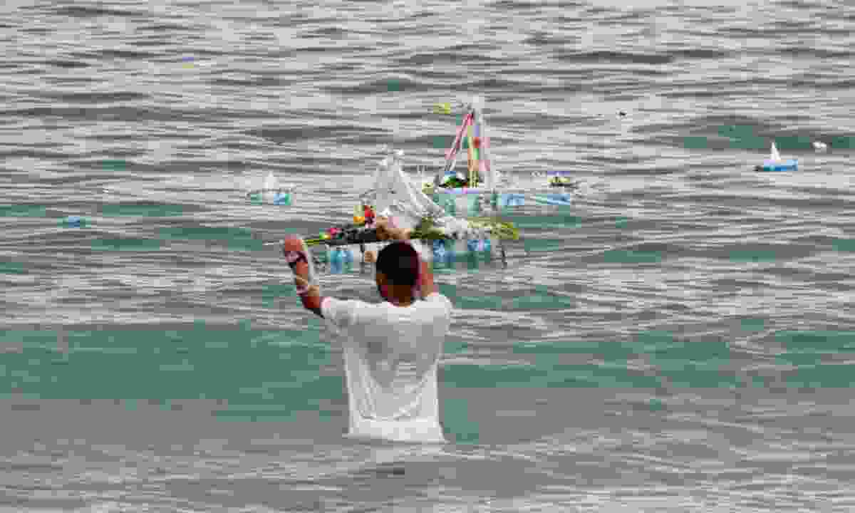 Guy setting boat in water to honour Yemanja (Dreamstime)
