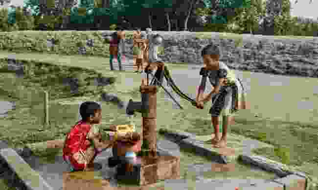 Kids in India using a water pump (Dreamstime)