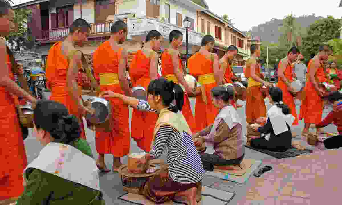 Buddhist monks collect alms (Dreamstime)