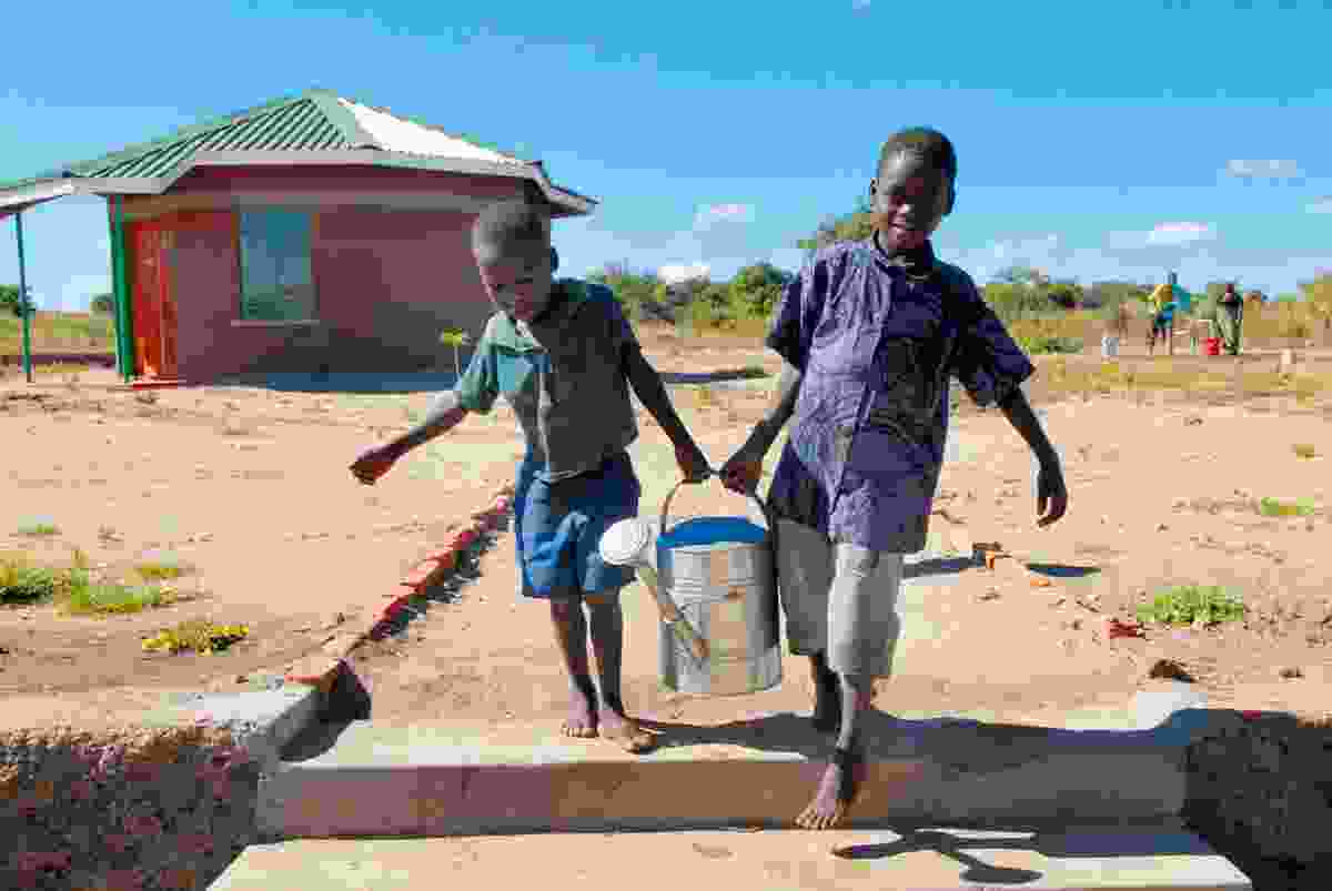 Orphans carrying a watering can in Malawi (Shutterstock)