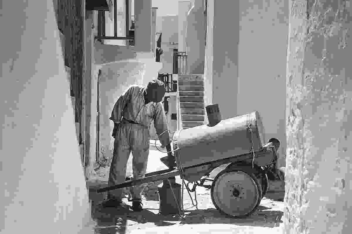Antonis Kousathanas makes a delivery of water in Chora. Before the introduction of these carts, water was delivered from pairs of buckets carried on each end of a pole that fit on a man's shoulders (Robert A. McCabe)