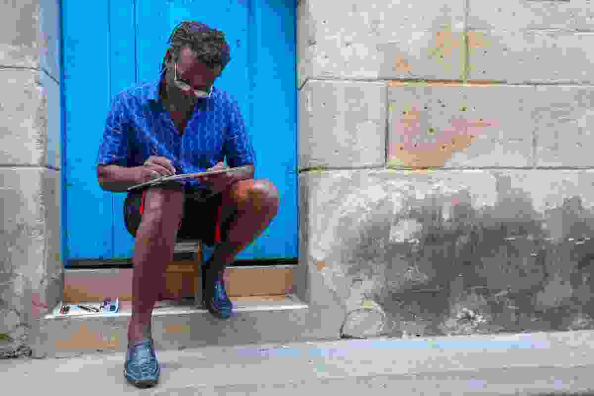An artist at work, carefully producing pencil drawings to sell to tourists (Graeme Green)