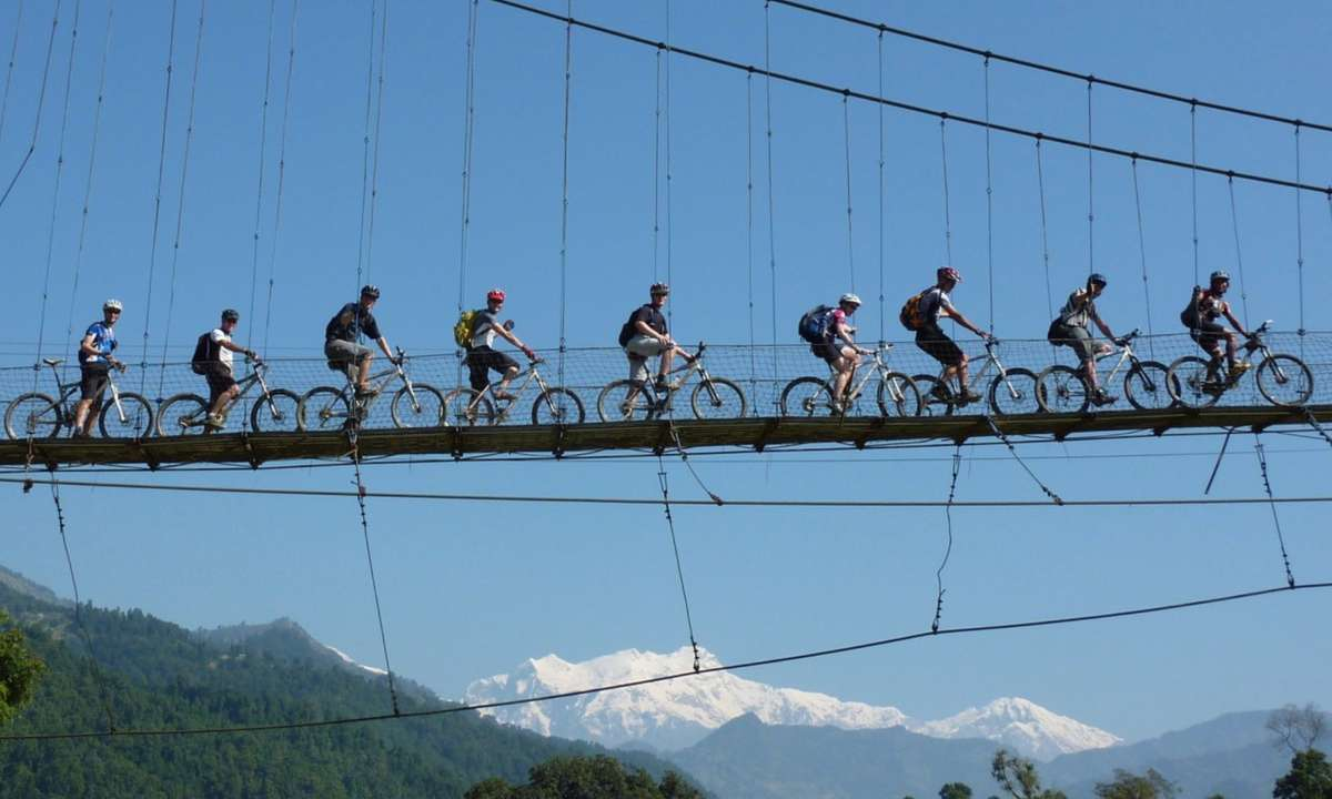 Cyclists crossing a suspension bridge on the 'road' to Kathmandu (KE Adventure Travel)