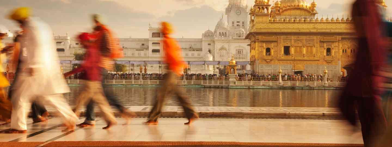 Pilgrims walking by the Amrit Sarovar (holy pool) (Dreamstime)