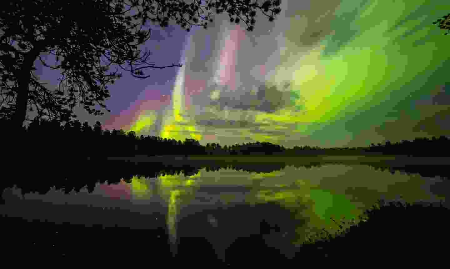 The Northern Lights reflected in a lake (TheAuroraZone.com)