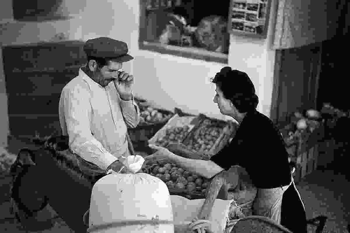 Assimina Kousathana at her family manavis, or green grocer shop, in serious negotiation with a farmer.  A few postcards hint at the beginning of a new era (Robert A. McCabe)
