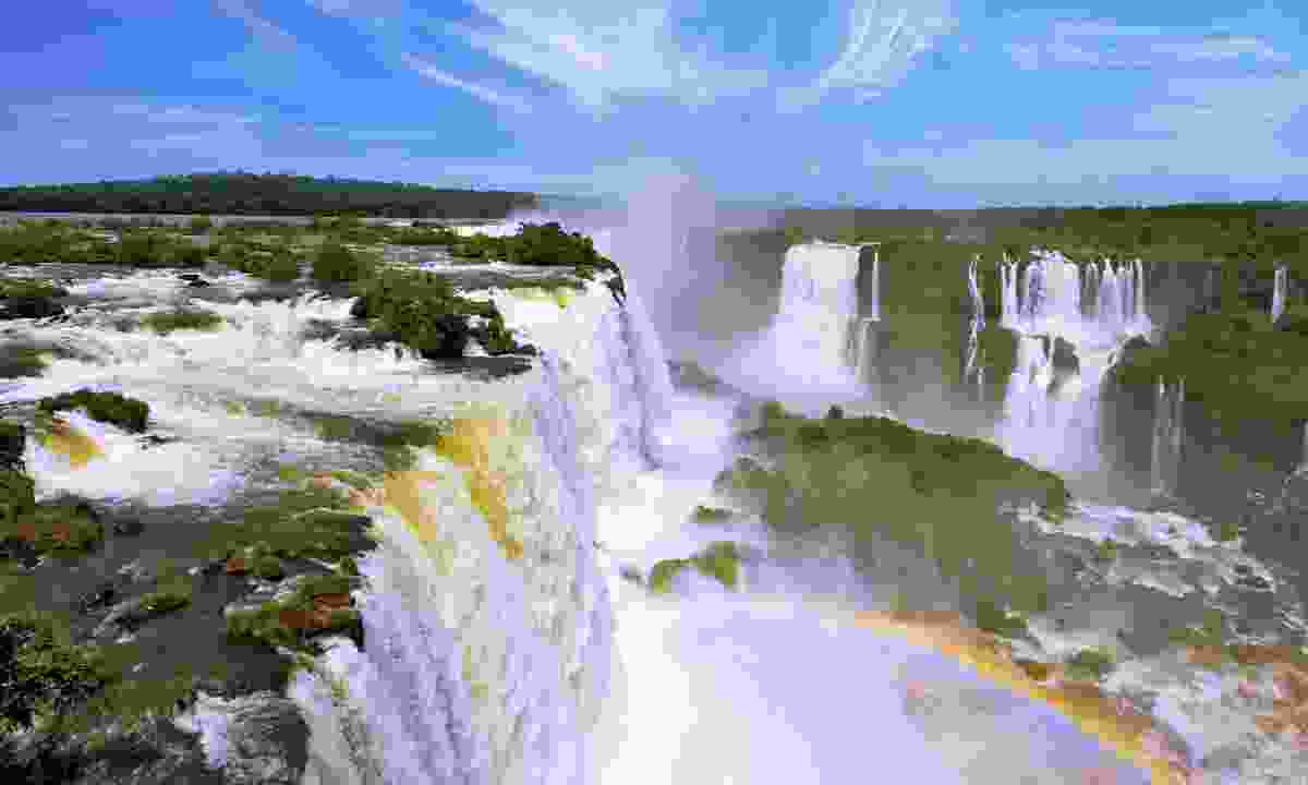 A rainbow arcs over the milky churn of  Iguazú Falls (Dreamstime)
