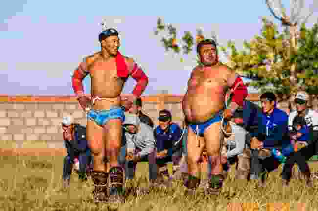 Mongolian wrestlers, in ceremonial regalia, wait to fight as part of the Naadam celebrations in Chandmani village (Marcus Westberg)
