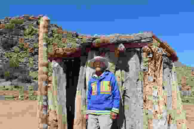 Jan, a Nama descendant stands beside his quiver tree hut near Springbok (Nora Wallaya)