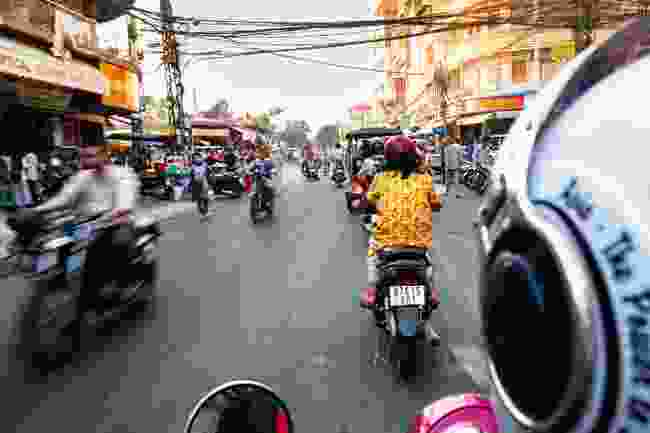 Whizzing through Phnom Penh's busy back streets (Alex Robinson)