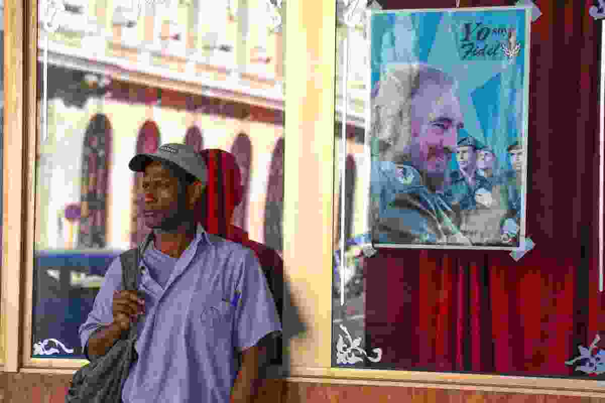 A local man waits for his bus, leaning against a window with a poster of Fidel (Graeme Green)