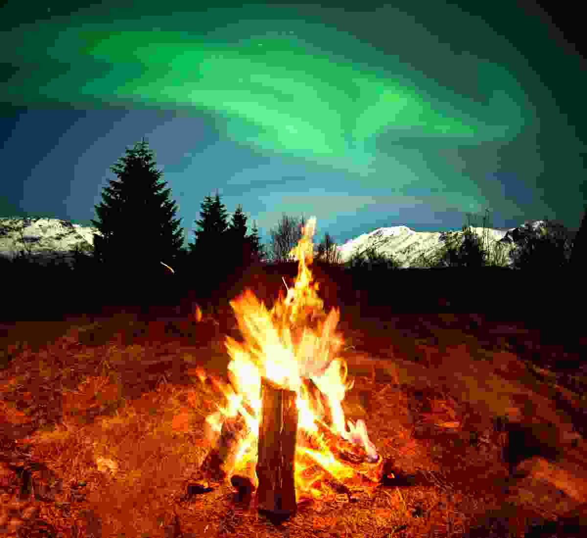 Watching the Northern Lights beside a campfire (Dreamstime)