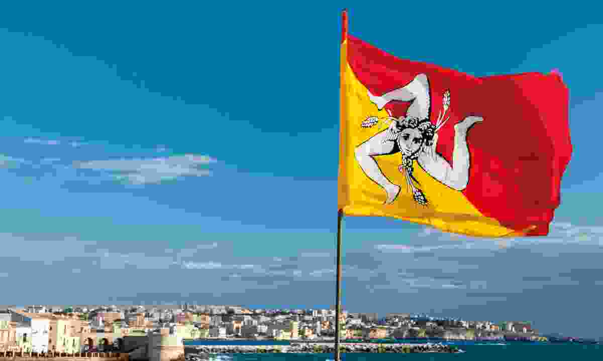 The waving flag of Sicily on the seafront  (Dreamstime)
