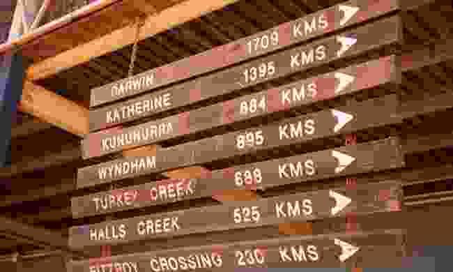 The sign at Willare Bridge Roadhouse promises many kilometres of adventure (Phoebe Smith)