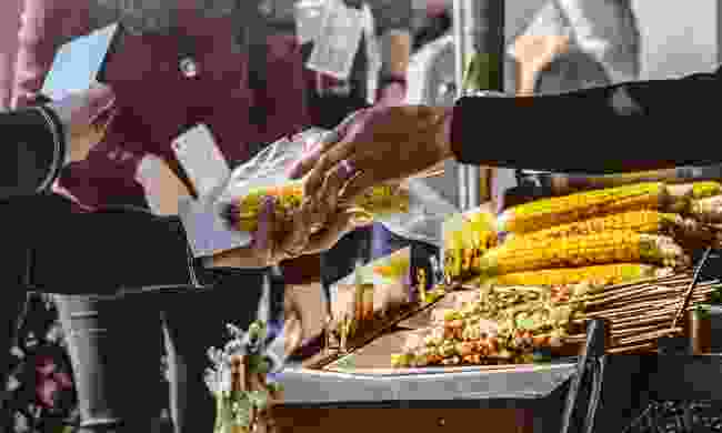 Vendor grilling corn (Shutterstock)