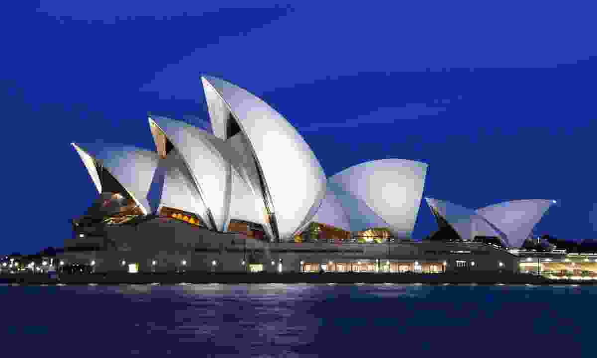 The sails of the Sydney Opera House illuminated at night (Shutterstock)