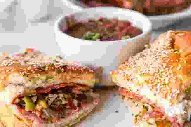 Muffuletta sandwich with cup of red beans in a New Orleans restaurant (Shutterstock)