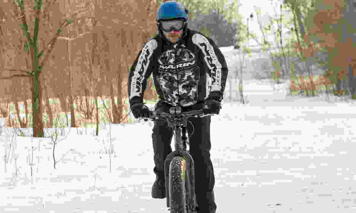 A man riding a fat bike on a snow trail in the wood (Dreamstime)