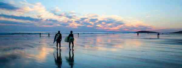 Dying of the light: Surfers squeezing in one last ride at the end of the day on the popular Rhossili beach (Graeme Green)