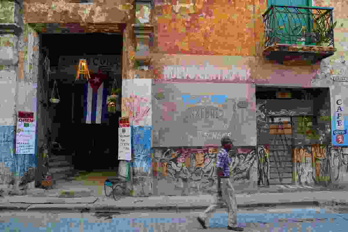 Man walking past the crumbly, colourful exterior of Somos Cuba restaurant (Graeme Green)