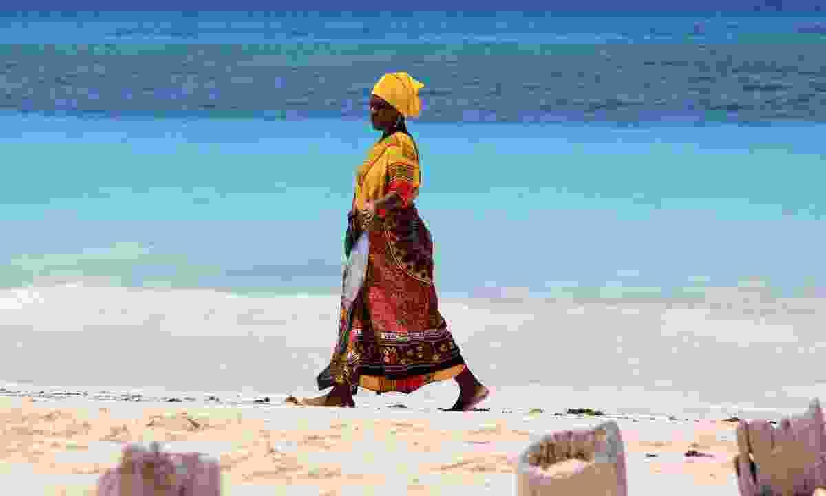 Woman dressed in kanga walking along a beach in Zanzibar (Dreamstime)