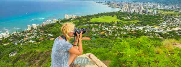 Woman photographing Honolulu from Diamond Head (Dreamstime)