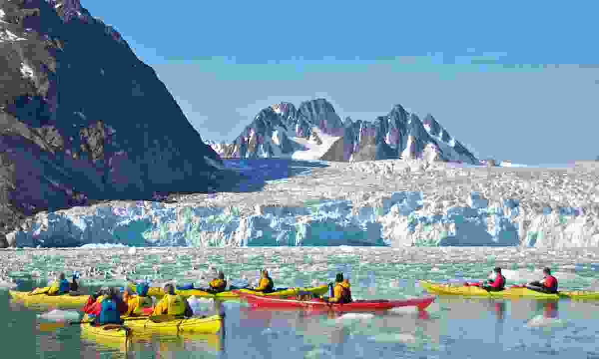 Travellers kayaking near Monaco Glacier on the calm water in Svalbard (Dreamstime)