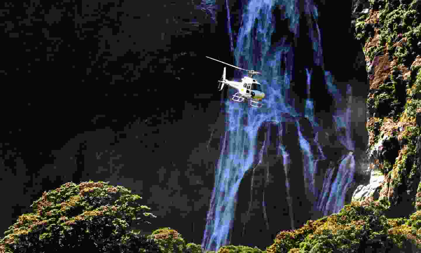 A helicopter flies over Fiordland, southern New Zealand (Shutterstock)