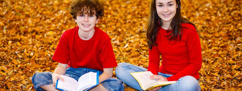 Kids reading under autumn leaves (Dreamstime)