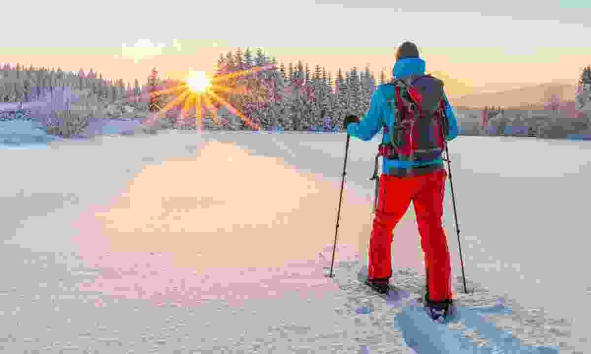 Snowshoe walker in powder snow with beautiful sunrise light (Dreamstime)