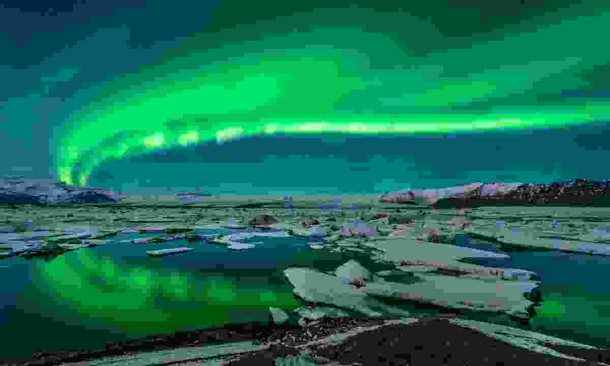 Northern lights over a lagoon by night (Tucan Travel)