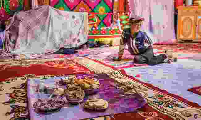 A boy inside a Kazakh yurt with typical sweets and snacks on the floor (Marcus Westberg)