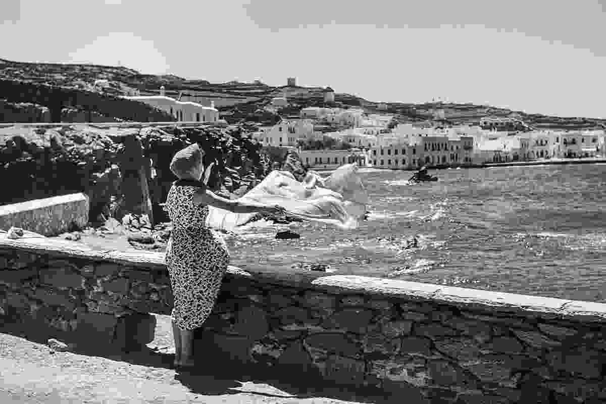 At Spitalia above the stone laundry basin, a woman dries her laundry, either holding it by hand or putting stones on it to hold it in place from the Meltemi wind. The rock in front of Saint Anna's beach is called Kolokitha which means pumpkin (Robert A. McCabe)