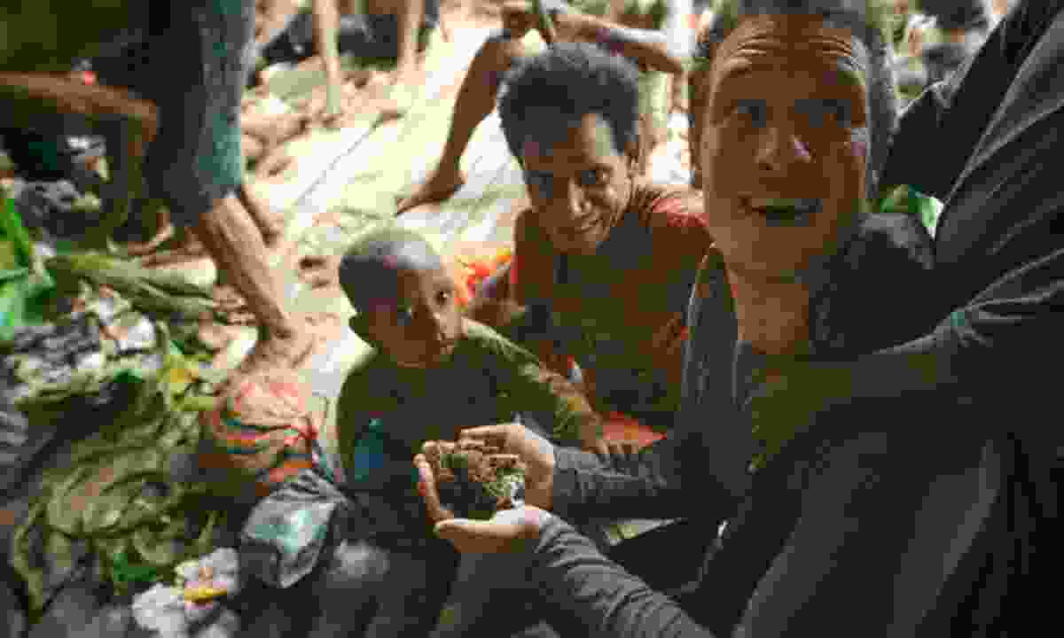 On arriving at a festival, Will is greeted by August and his sons with handfuls of fresh sago grubs (BBC/ KEO Films)