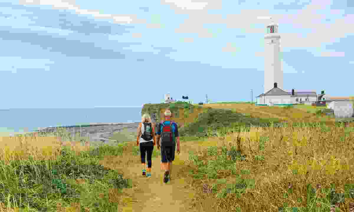 Lighting the way: Hikers on the Wales Coast Path passing in front of Nash Point Lighthouse (Graeme Green)