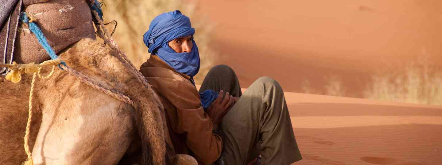 A Berber man and his camel (Dreamstime)