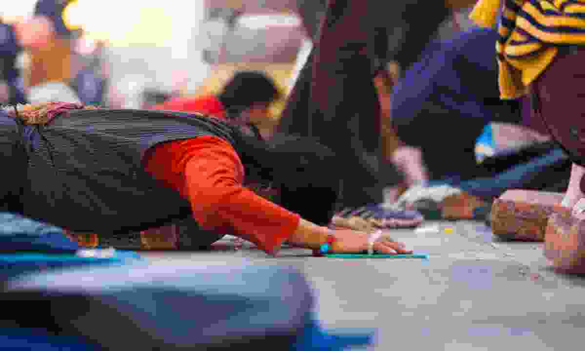 ibetan prostrator lies flat on her stomach at Jokhang temple (Dreamstime)