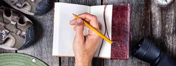 Writing in a travel journal (Dreamstime)