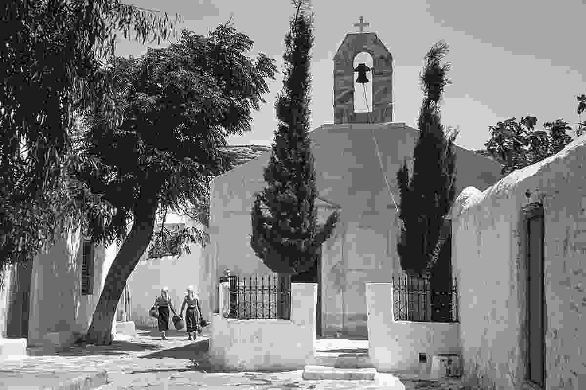 The twin church of Saint Barbara, (door on left behind the cypress tree), and Saint Fanourios, door on right. On the left behind the tree (now gone) is the chapel of Saint George and the Three Wells. Legend has it that if a girl offered a man water from the middle well he would ask her to marry him. The dress of the young women points to their coming from the countryside, perhaps with farm produce for the market  (Robert A. McCabe)