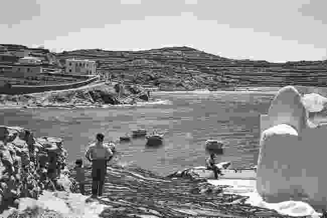 At the church of Saint Charalambos a local family of fishermen dry their nets. Today the entrance to the Xenia hotel is set into the wall on the left and the hillsides have been unmercifully covered with villas. The beach of Megali Ammos or Big Sand is in the distance (Robert A. McCabe)