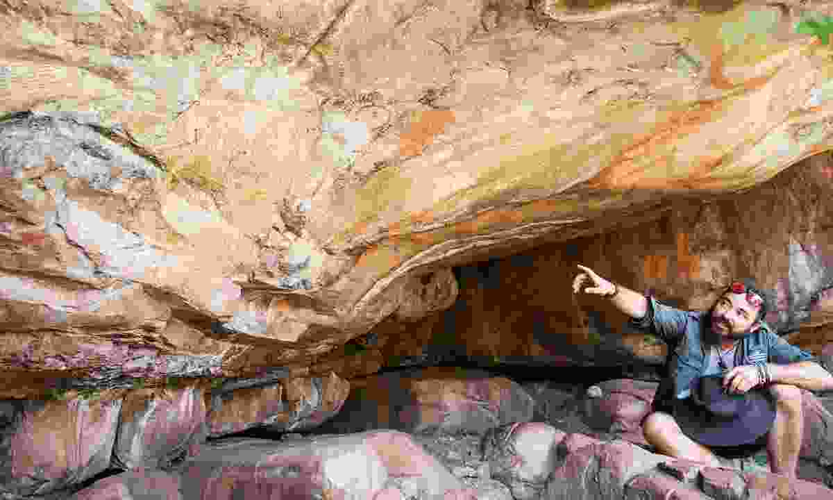 Duffman points out cave paintings found after a walk from an innocuous turning off the main road (Phoebe Smith)