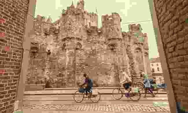 Cyclists riding past the 12th century Gravensteen castle (Shutterstock)