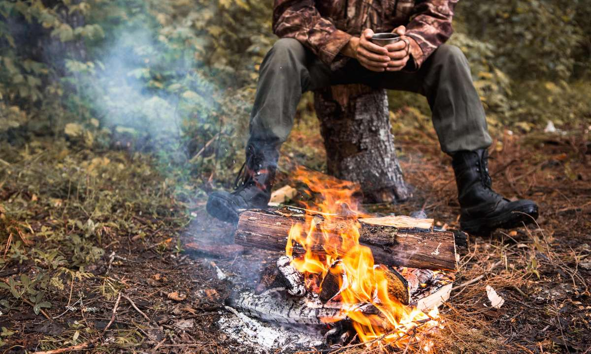 Sitting by the fire in the forest (Dreamstime)