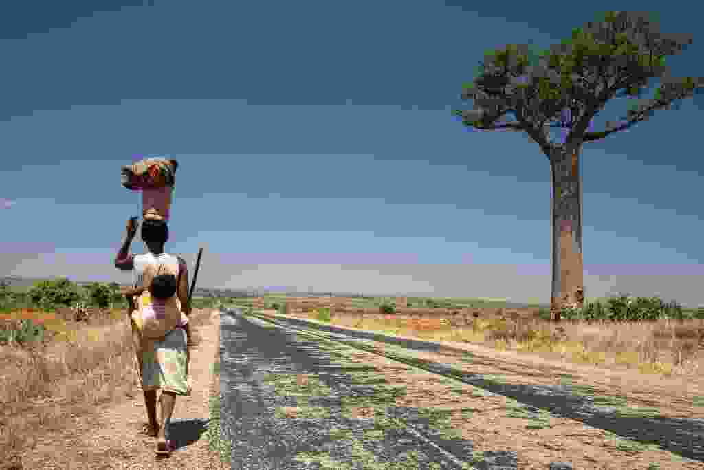 A woman with her baby walks beside the RN7 road near Zombitse-Vohibasia NP (William Gray)
