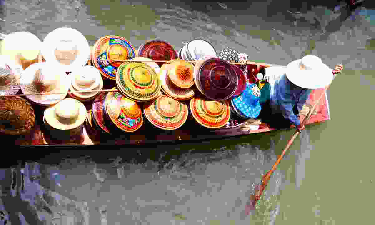 Hat seller on Damnoen Saduak Floating Market near Bangkok (Dreamstime)