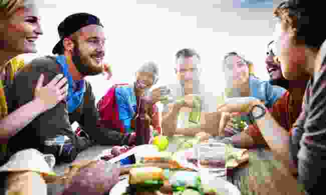 Group of friends enjoying a meal (Shutterstock)