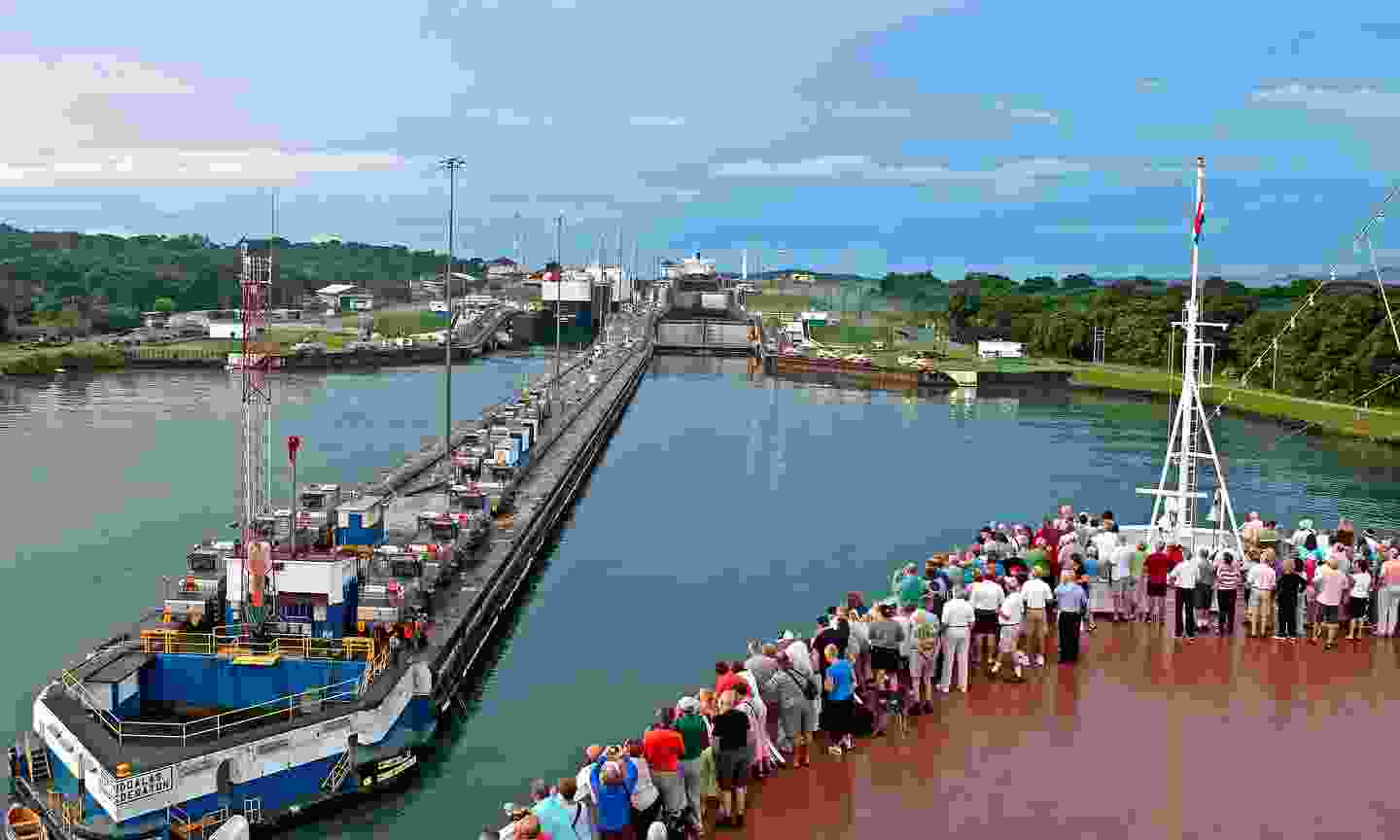 Tourists stand on bow of a cruise ship as it enters first lock of Panama Canal (Shutterstock)
