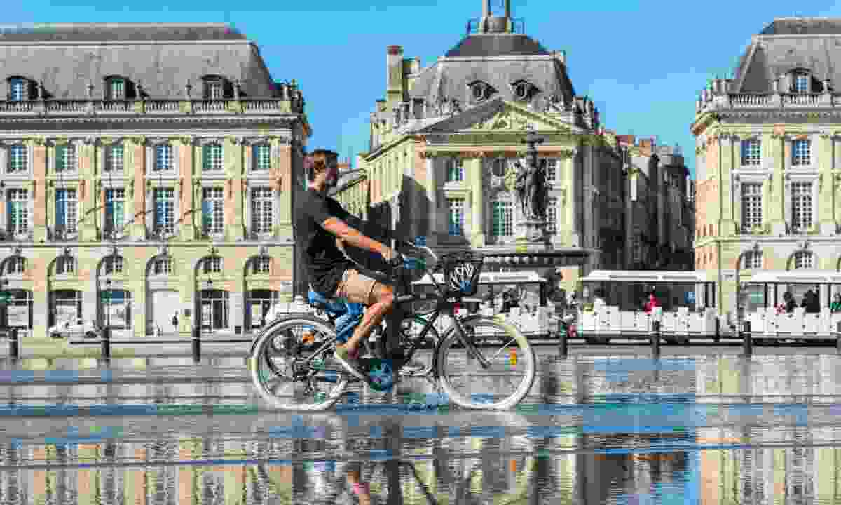 Riding bicycles in the mirror fountain in front of Place de la Bourse (Shutterstock)